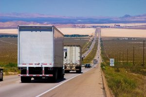 photo of semi-trucks and cars on an Interstate highway.